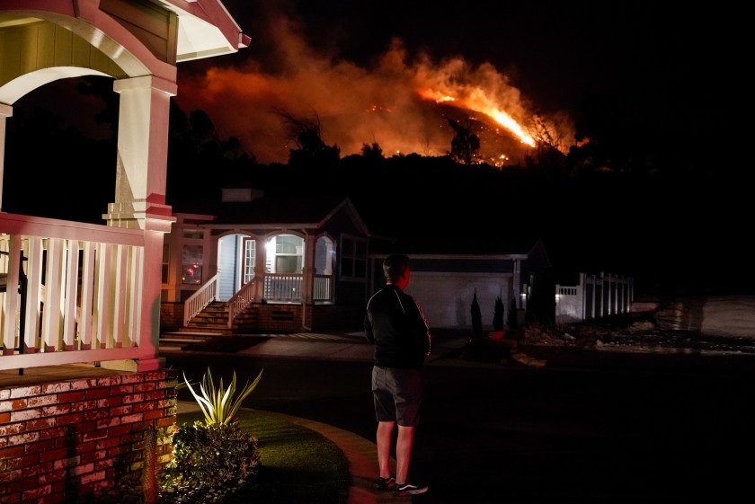 Oakridge Estates resident Manuel Negrete gazes at the Saddleridge fire as his neighbors evacuate on Oct. 10, 2019. (Credit: Kent Nishimura / Los Angeles Times)