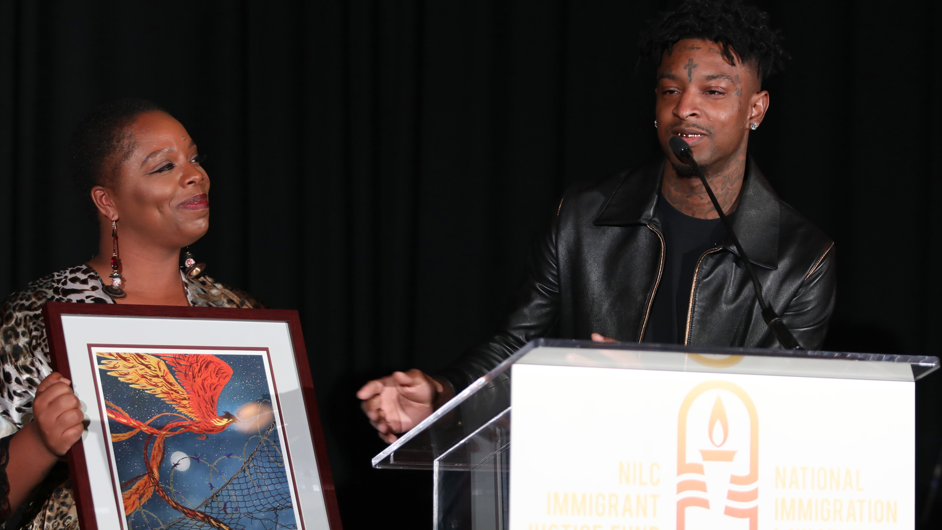 Patrisse Cullors, co-founder of Black Lives Matter presents 21 Savage with an award at the National Immigration Law Center's Courageous Luminaries Awards on Oct. 3, 2019 in Los Angeles. (Credit: Jerritt Clark/Getty Images for NILC)
