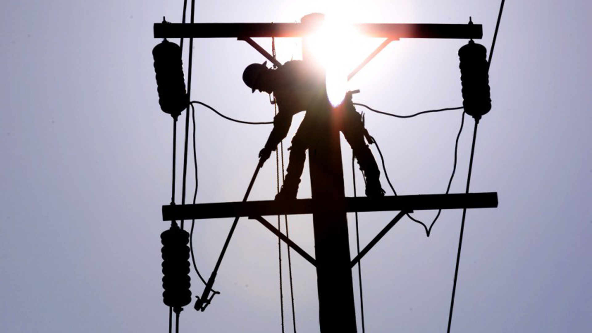 A Southern California Edison lineman grounds a power line in La Habra. The utility is considering shutting off power to 32,500 customers ahead of high winds.(Credit: Los Angeles Times)