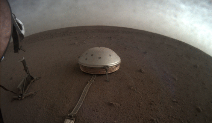 Clouds drift over the dome-covered seismometer, known as SEIS, belonging to NASA's InSight lander, on Mars. (Credit: NASA)
