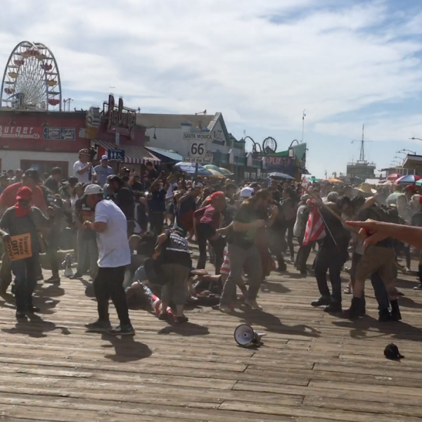 Screaming protestors disperse after what appears to be a cloud of pepper spray is seen in the crowd at Santa Monica Pier on Oct. 19, 2019. (Credit: KTLA)