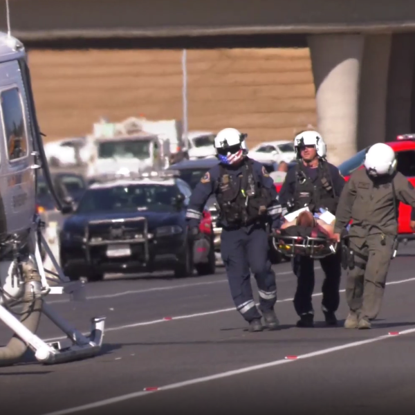 Paramedics transport an injured Ontario Police officer to a helicopter on Interstate 215 in the Grand Terrace area on Oct. 22, 2019. (Credit: RMG News)