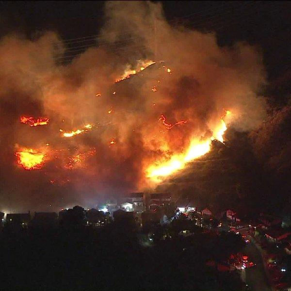Firefighters battle a wildfire near homes in Sylmar on Oct. 10, 2019. (Credit: KTLA)