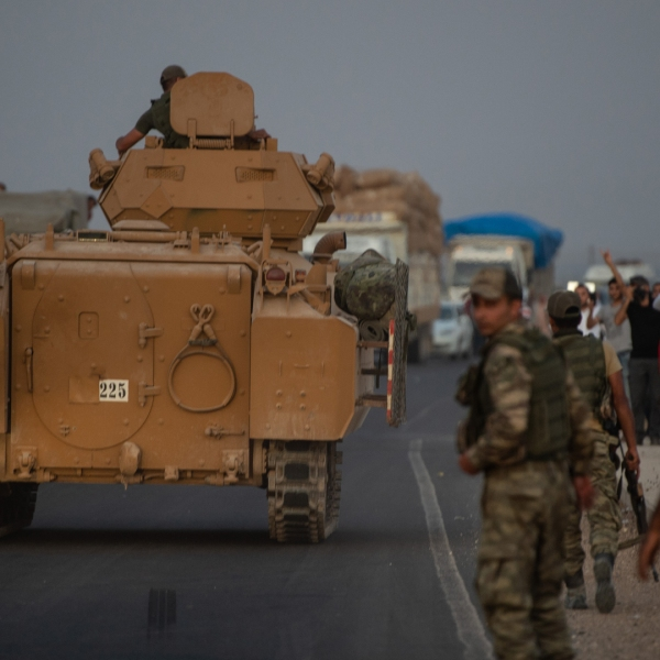 People wave as Turkish soldiers prepare to cross the border into Syria on October 09, 2019 in Akcakale, Turkey. The military action is part of a campaign to extend Turkish control of more of northern Syria, a large swath of which is currently held by Syrian Kurds, whom Turkey regards as a threat. (Credit: Burak Kara/Getty Images)