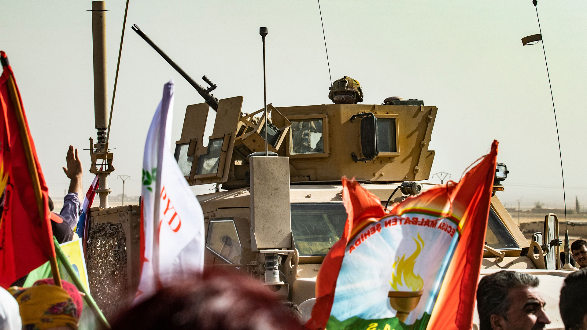 """A soldier sits atop an armored vehicle during a demonstration by Syrian Kurds against Turkish threats at a US-led international coalition base on the outskirts of Ras al-Ain town in Syria's Hasakeh province near the Turkish border on October 6, 2019. - Ankara had reiterated on October 5 an oft-repeated threat to launch an """"air and ground"""" operation in Syria against a Kurdish militia it deems a terrorist group. (Credit: Delil Souleiman/AFP/Getty Images)"""