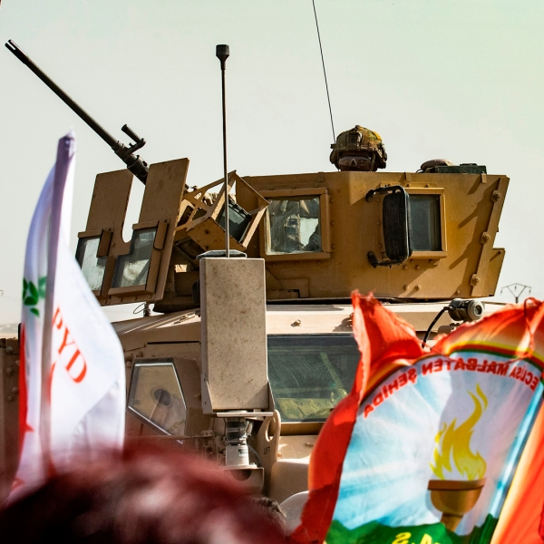 "A soldier sits atop an armored vehicle during a demonstration by Syrian Kurds against Turkish threats at a US-led international coalition base on the outskirts of Ras al-Ain town in Syria's Hasakeh province near the Turkish border on October 6, 2019. - Ankara had reiterated on October 5 an oft-repeated threat to launch an ""air and ground"" operation in Syria against a Kurdish militia it deems a terrorist group. (Credit: Delil Souleiman/AFP/Getty Images)"