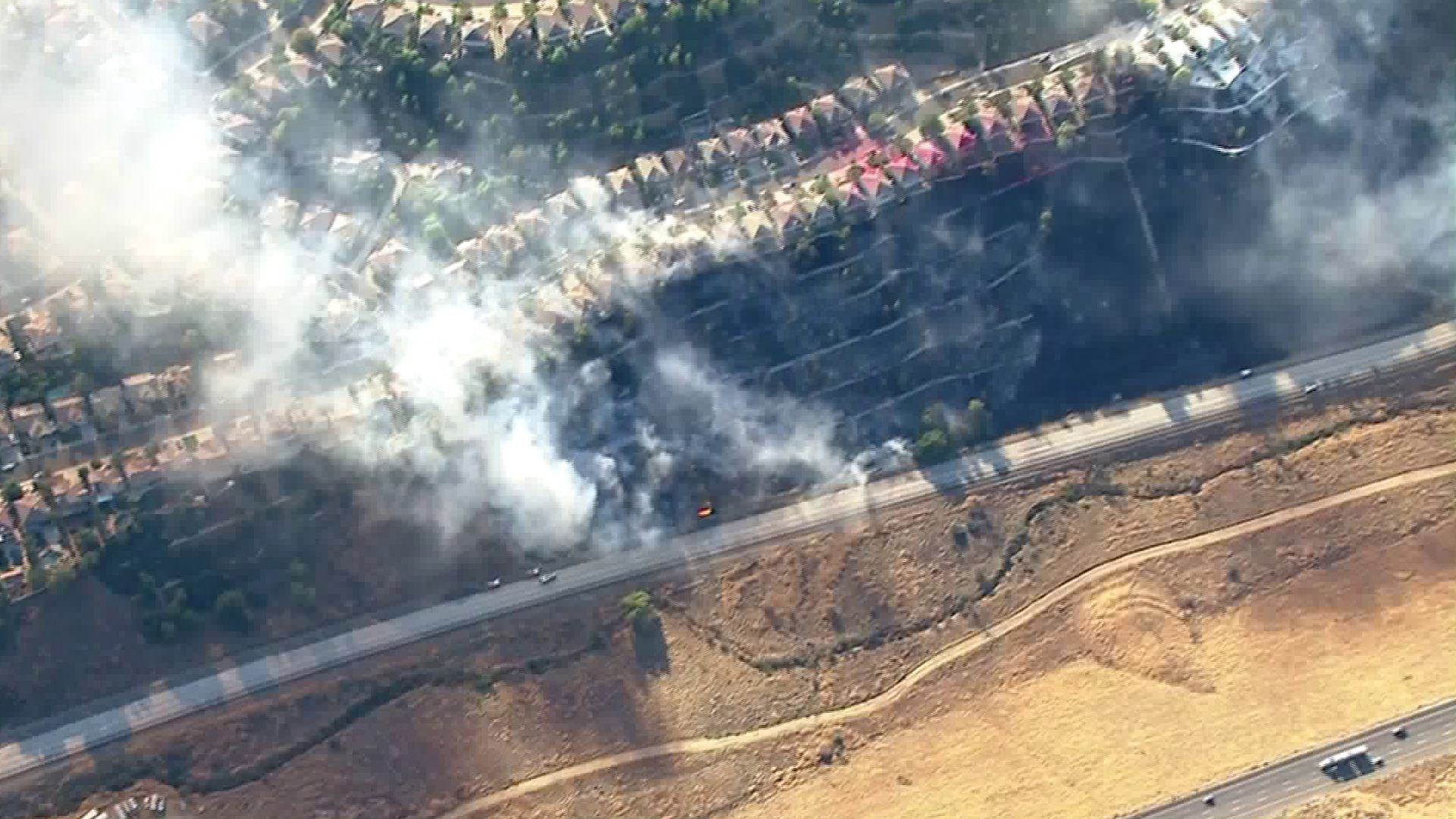 A home burns off the Old Road next to the 5 Freeway in the Old Fire in the Castaic area on Oct. 24, 2019. (Credit: KTLA)