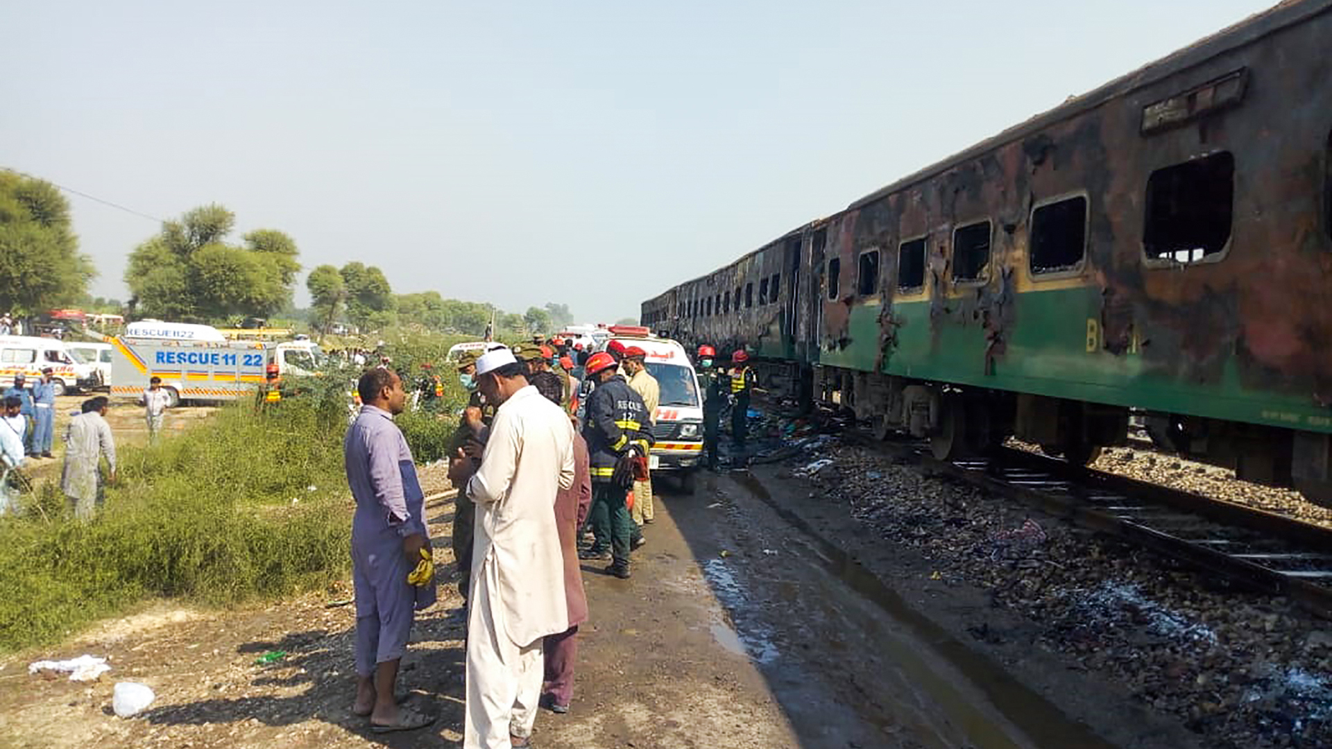 Rescue workers gather beside the burnt-out train carriages after a passenger train caught on fire near Rahim Yar Khan in Punjab province on October 31, 2019. (Credit: AFP via Getty Images)