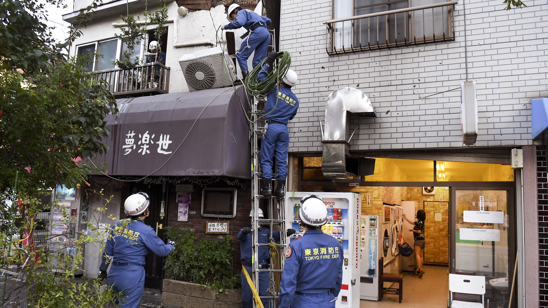 Tokyo Fire Department workers help repair damage in the aftermath of Typhoon Hagibis, as a woman (R) uses a laundry machine in a shop in Kawasaki on October 13, 2019. (Credit: William West/AFP/Getty Images)