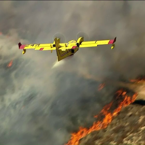 An aircraft drops water on the Jake Fire in the Santa Clarita area on Nov. 6, 2019. (Credit: KTLA)