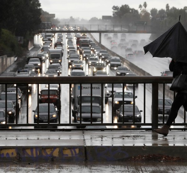 A pedestrian walks on an overpass as motorists clog the 101 Freeway during heavy rain in an undated photo. (Credit: Mel Melcon / Los Angeles Times)