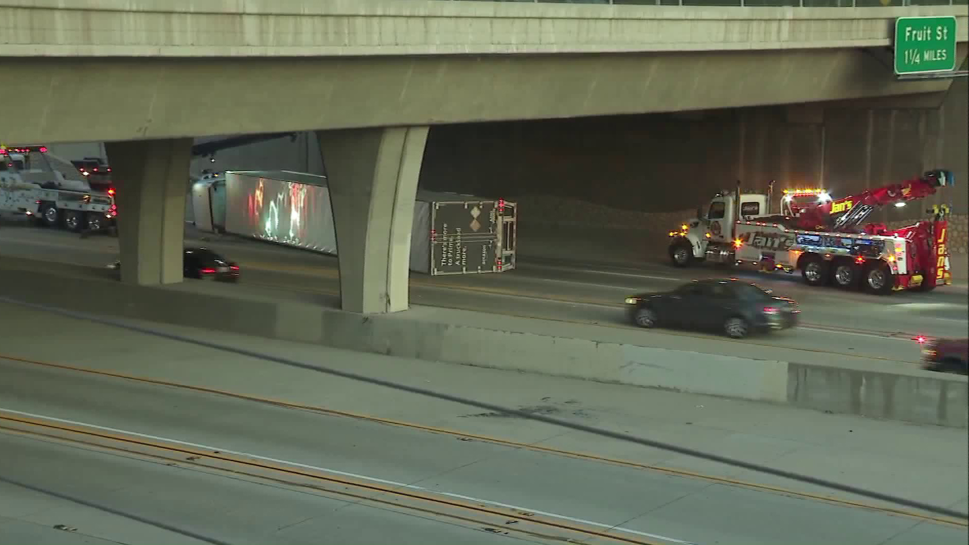 An overturned truck is see under an overpass on the westbound 210 Freeway in Claremont. (Credit: KTLA)