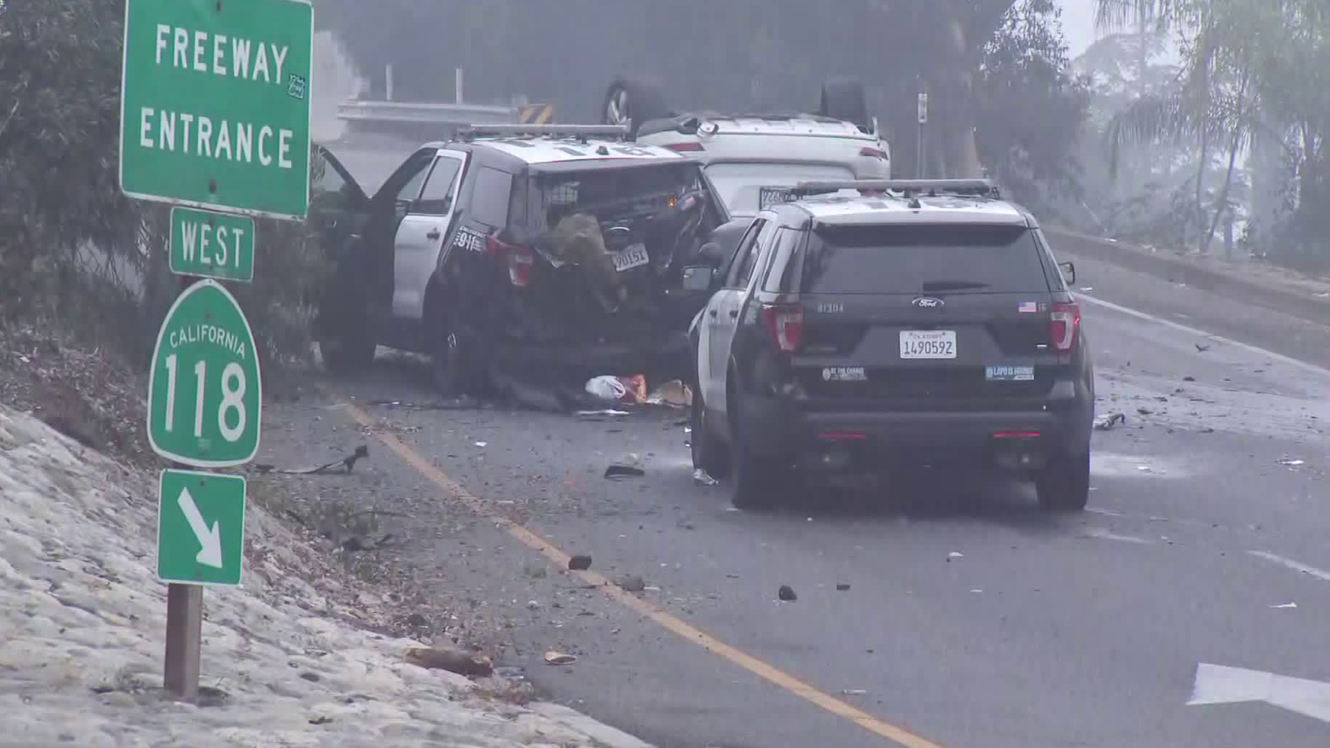 A heavily damaged Los Angeles police vehicle is seen behind a white Mercedes SUV that came to rest upside-down after crashing in Pacoima on Nov. 11, 2019. (Credit: KTLA)