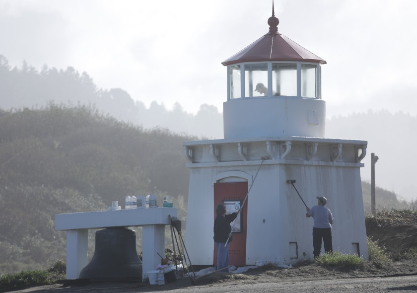 Trinidad Civic Club volunteers Patti Fleschner, left, Mary Kline and Gary Stillman, top, clean the Trinidad Memorial Lighthouse at its temporary location near the parking lot for Trinidad Harbor. It was moved from its original bluff-top location because of a slow-moving landslide.(Credit: Myung J. Chun / Los Angeles Times)