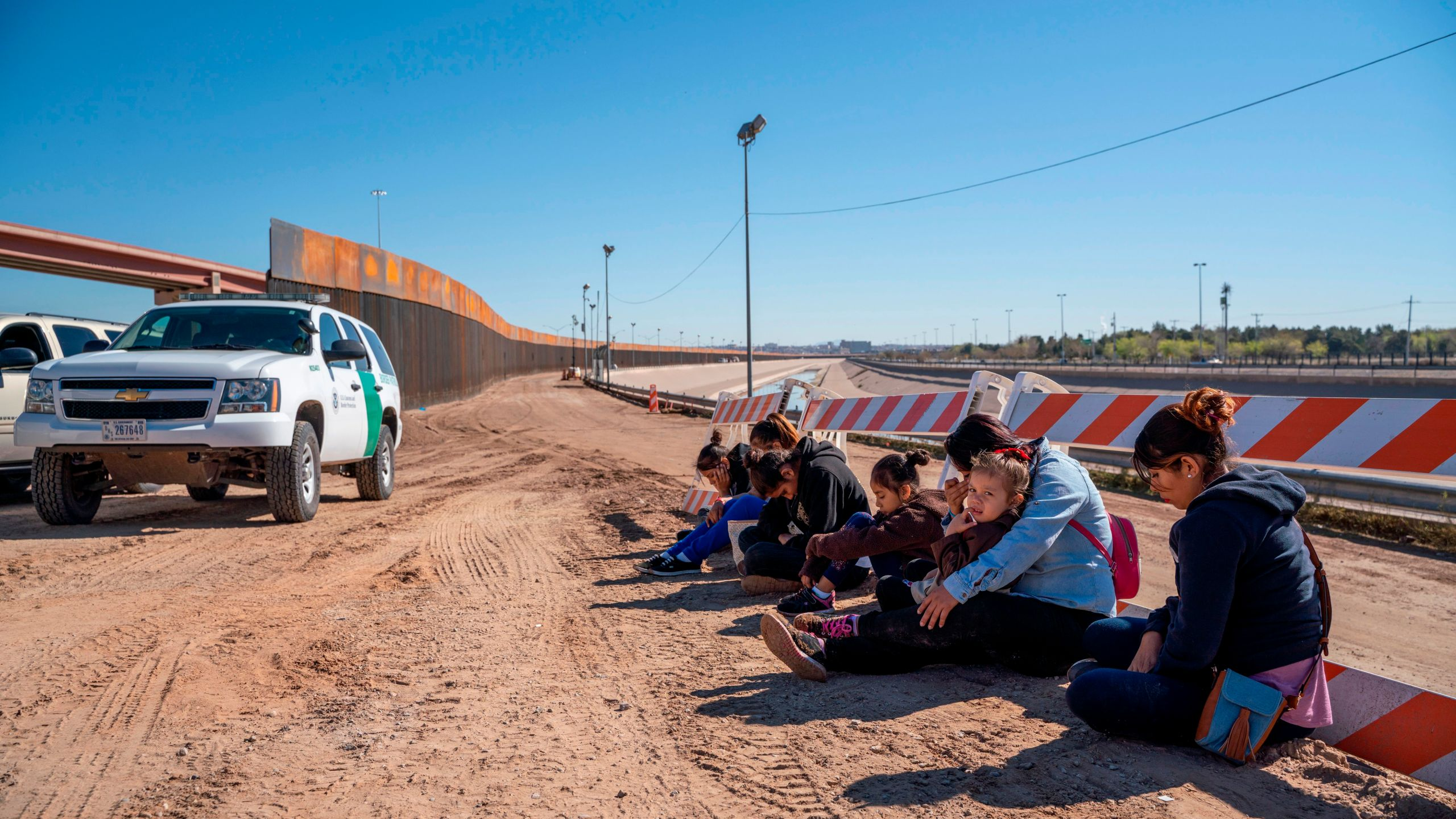 Salvadoran migrants wait for a transport to arrive after turning themselves into U.S. Border Patrol by border fence under construction in El Paso, Texas, on March 19, 2019. (Credit: Paul Ratje / AFP / Getty Images)