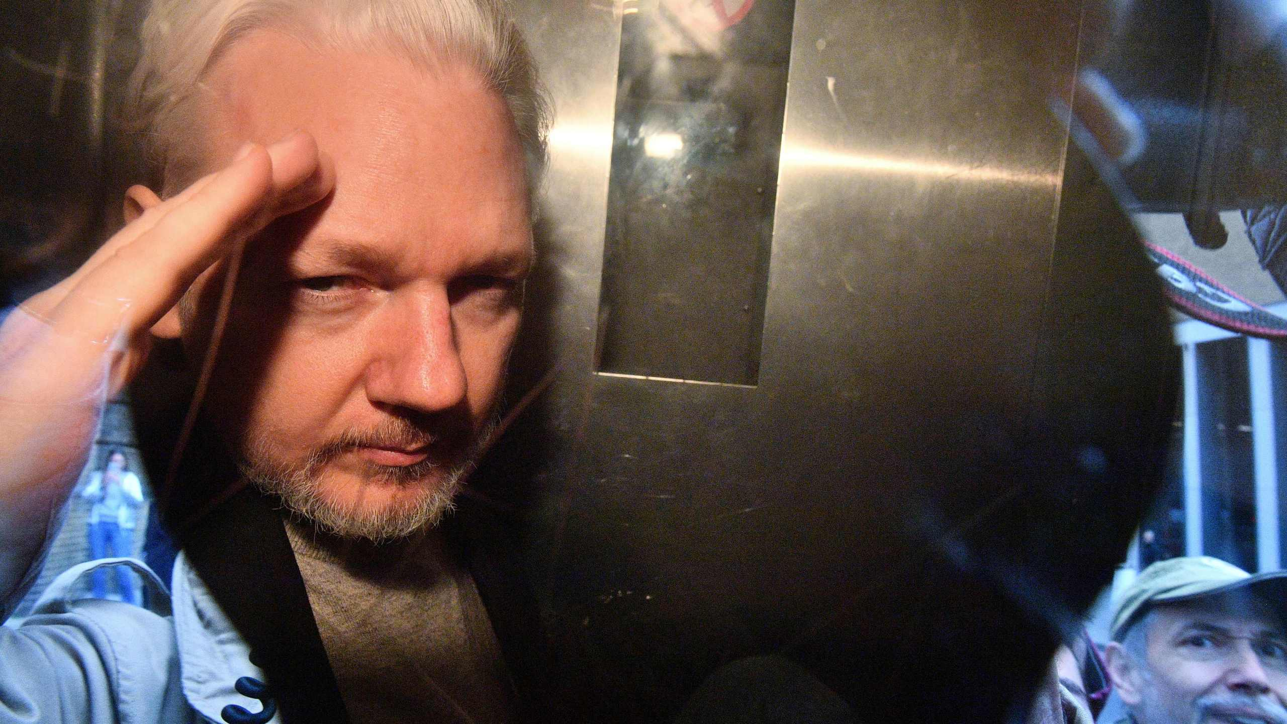 WikiLeaks founder Julian Assange gestures from the window of a prison van as he is driven out of Southwark Crown Court in London on May 1, 2019. (Credit: DANIEL LEAL-OLIVAS/AFP via Getty Images)