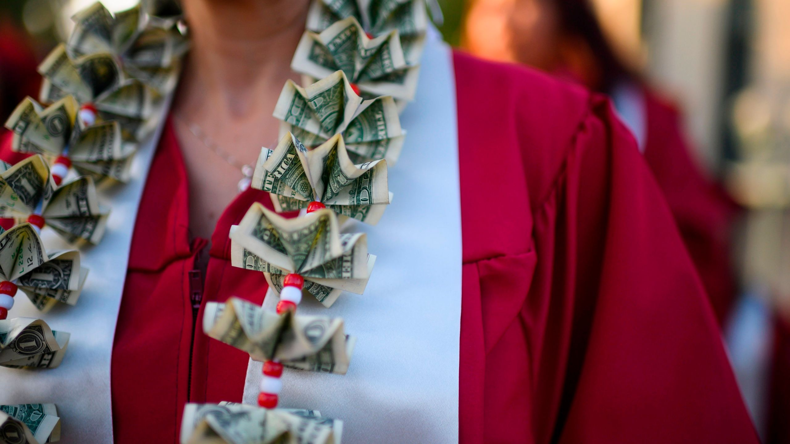 A graduate wears a lei made of U.S. dollar bills at the Pasadena City College graduation ceremony on June 14, 2019. (Credit: Robyn Beck / AFP / Getty Images)