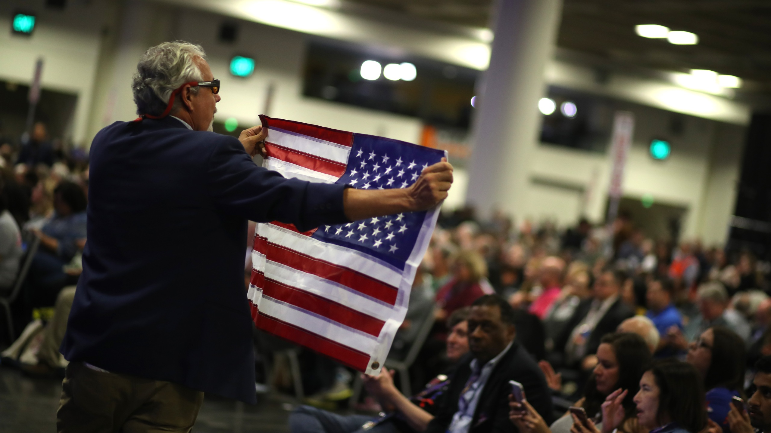 An attendee carries an American flag during the California Democrats 2019 State Convention at the Moscone Center on June 1, 2019, in San Francisco. (Credit: Justin Sullivan/Getty Images)