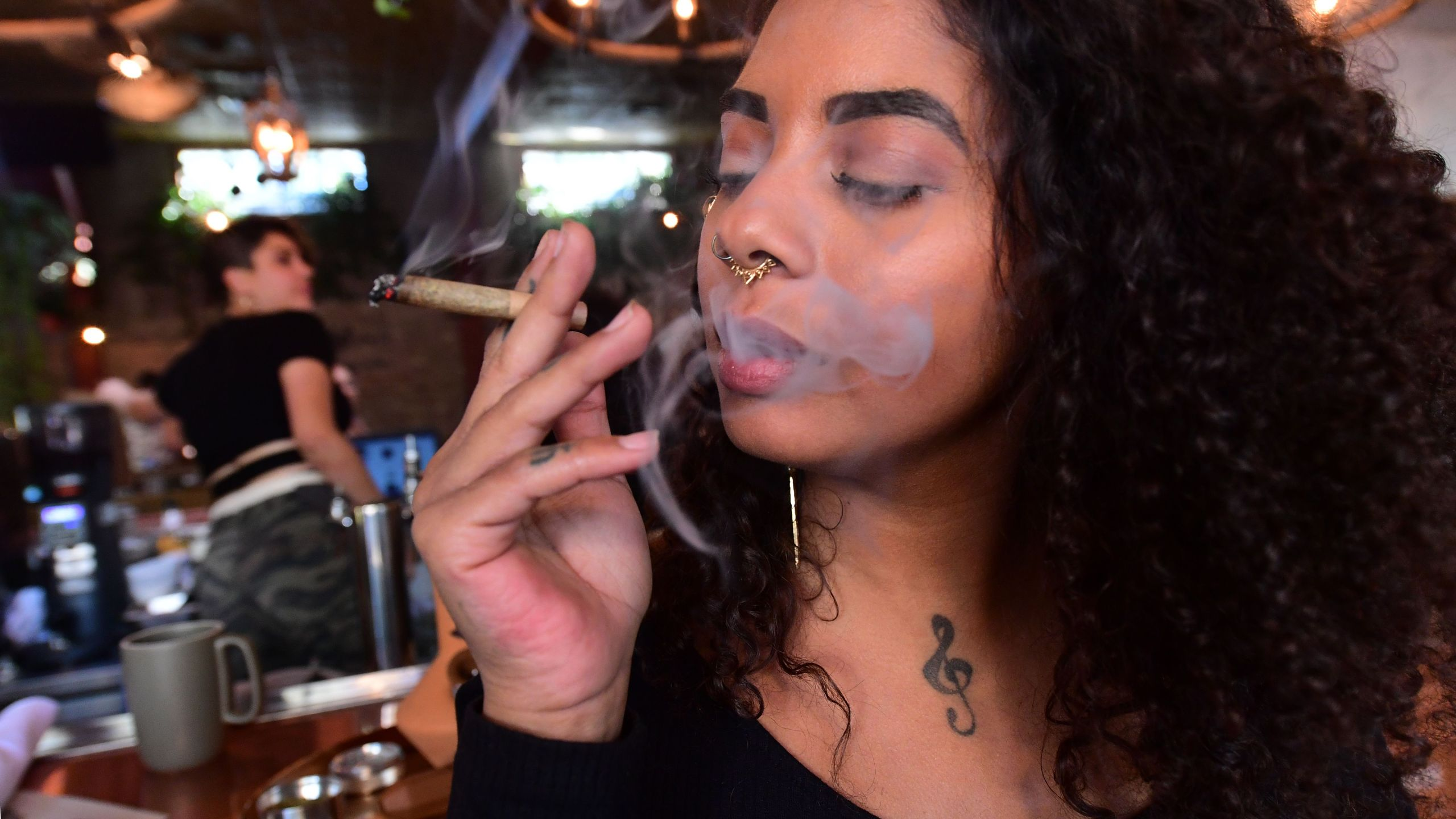 Kush Doleo smokes a joint at the Lowell Cafe in West Hollywood on Sept. 30, 2019, a day before its official opening. (Credit: Frederic J. Brown / AFP / Getty Images)