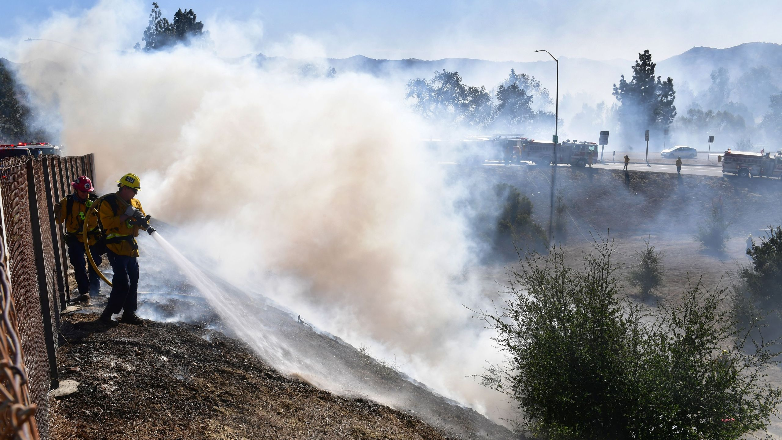 A firefighter sprays water on charred hillside near homes and the 118 Freeway in Simi Valley on Oct. 30, 2019. (Credit: Frederic J. Brown / AFP / Getty Images)