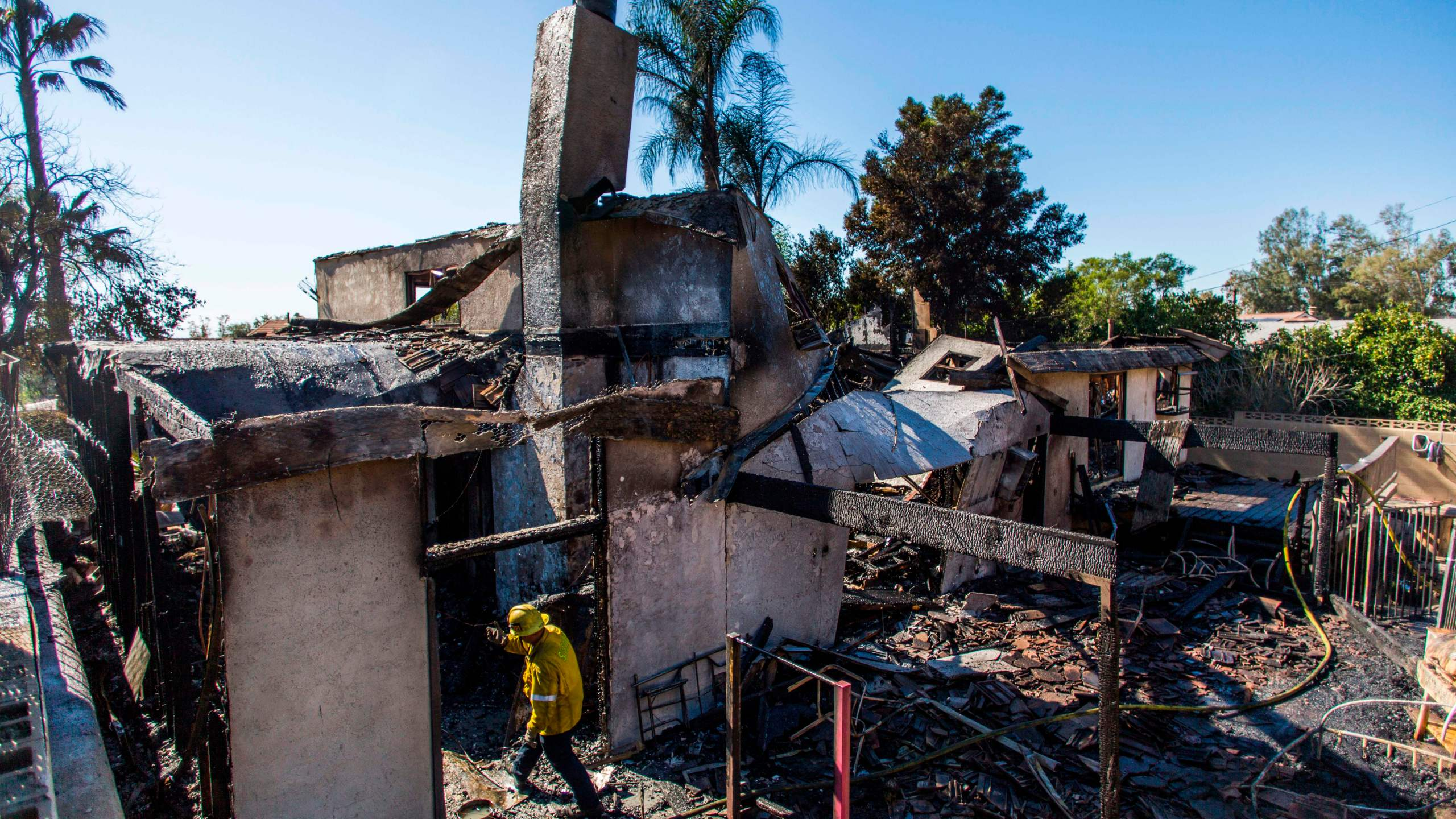 Firefighters look at what is left of a home on Viento Way after several homes were burned by the Hillside Fire in San Bernardino on Oct. 31, 2019. (Credit: Apu Gomes / AFP / Getty Images)