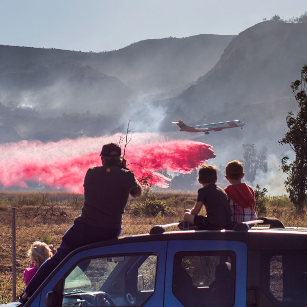 A family watches an air tanker dropping fire retardant battling the Maria Fire in Santa Paul on Nov. 1, 2019. (Credit: Apu Gomes / AFP / Getty Images)