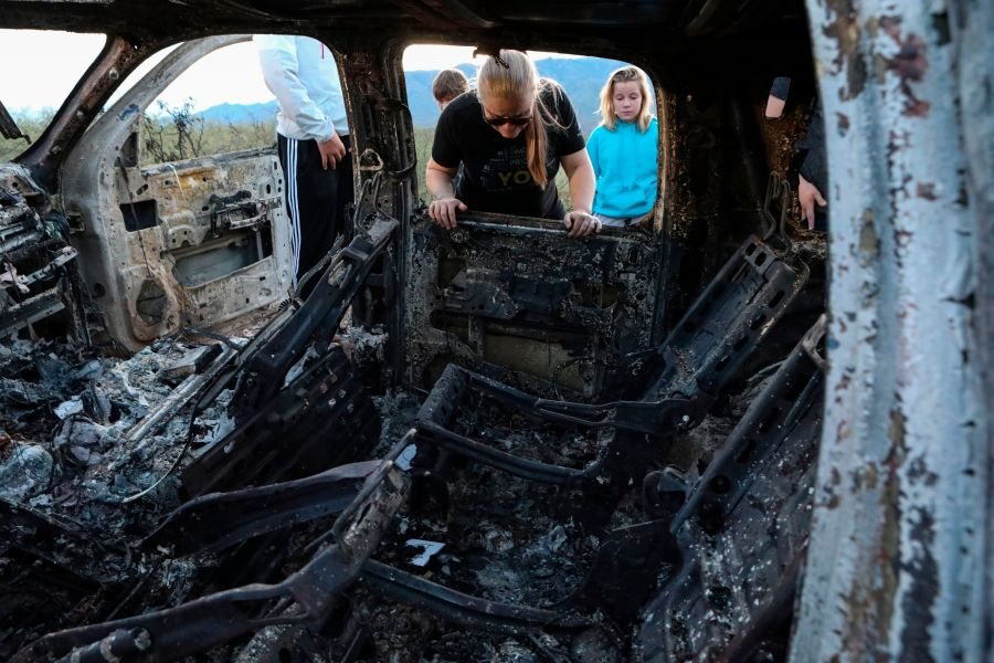 Members of the LeBaron family view the burned car where their relatives were killed and burned during an ambush in Bavispe, Sonora mountains, Mexico, on Nov. 5, 2019. (Credit: Herika Martinez / AFP / Getty Images)