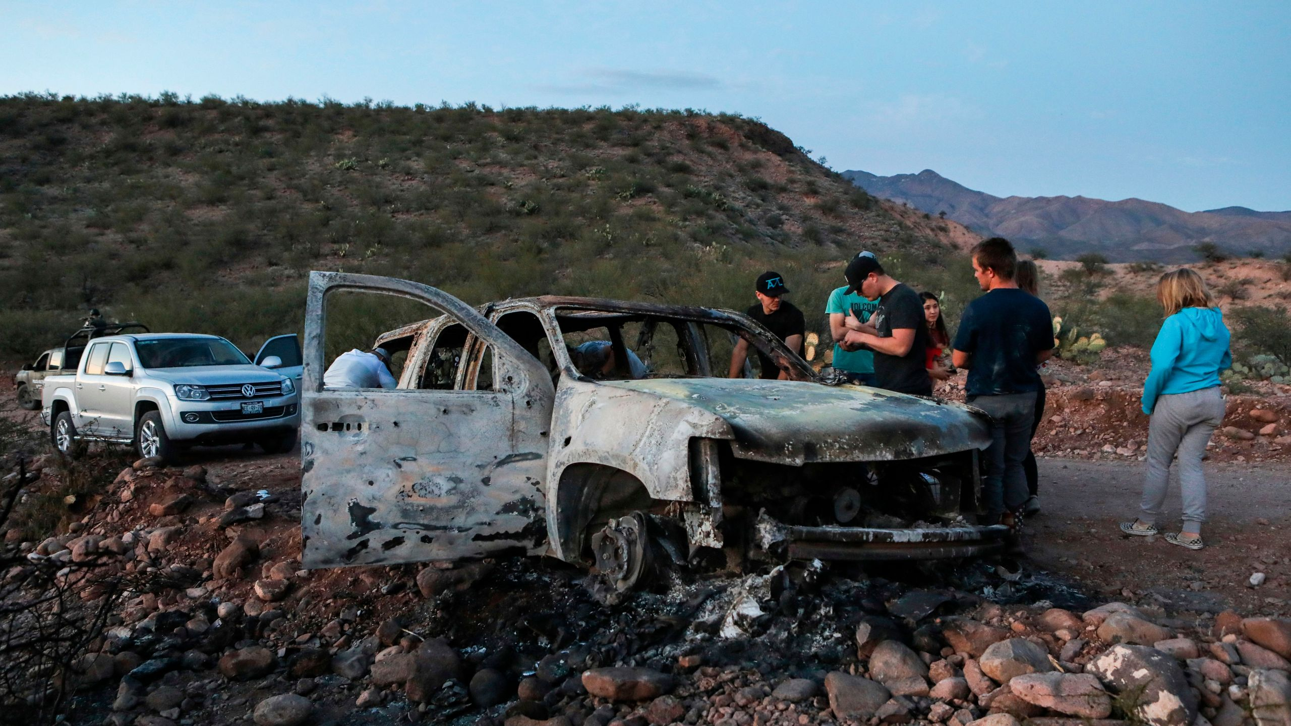 Members of the Lebaron family mourn as they look at the burned car where part of the nine murdered members of their family were killed and burned during an ambush in Bavispe, Sonora mountains, Mexico, on Nov.5, 2019. (Credit: HERIKA MARTINEZ/AFP via Getty Images)