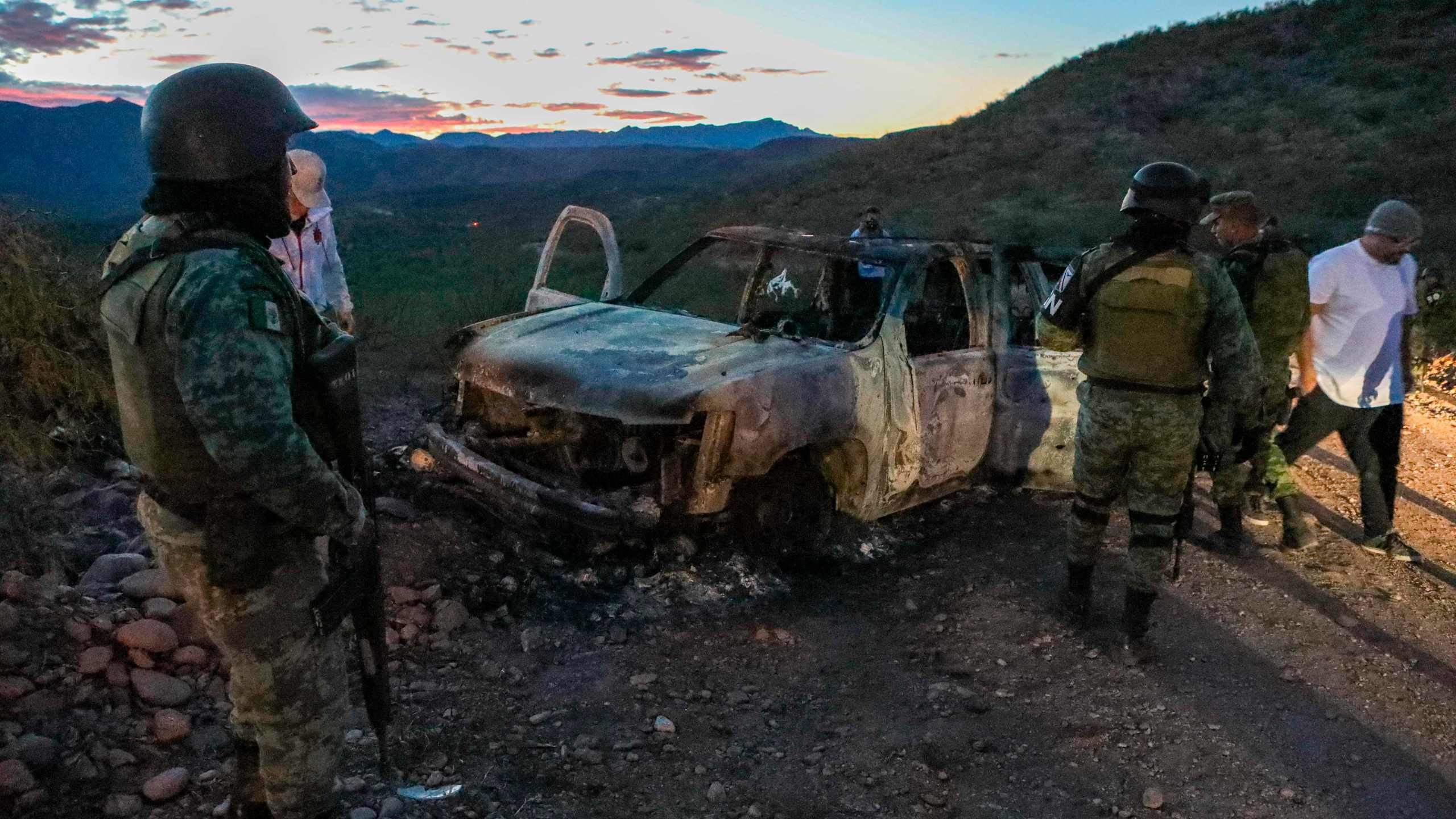 People stand near the burned car where members of the LeBaron family were killed and burned during an ambush in Bavispe, Sonora mountains, Mexico, on Nov. 5, 2019. (Credit: Herika Martinez / AFP / Getty Images)