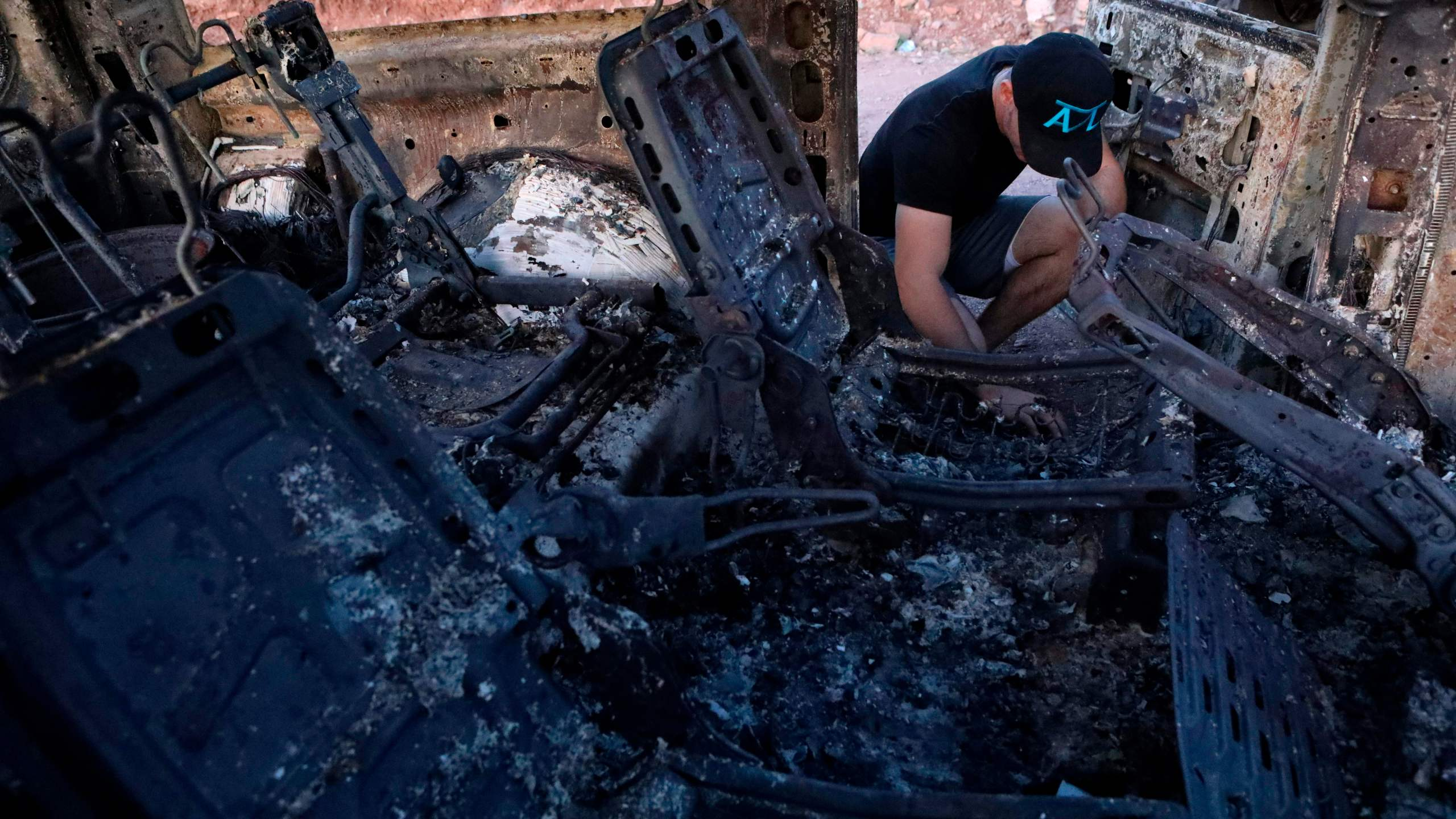 A member of the LeBaron family looks at the burned car where some of nine relatives were killed and burned during an ambush in Bavispe, Sonora mountains, Mexico, on Nov. 5, 2019. (Credit: Herika Martinez / AFP / Getty Images)
