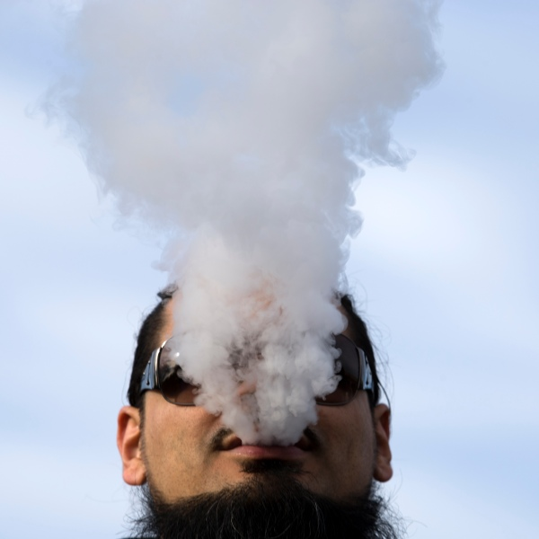 A demonstrator vapes during a rally outside the White House protesting a proposed vaping flavor ban on Nov. 9, 2019. (Credit: Jose Luis Magana / AFP / Getty Images)