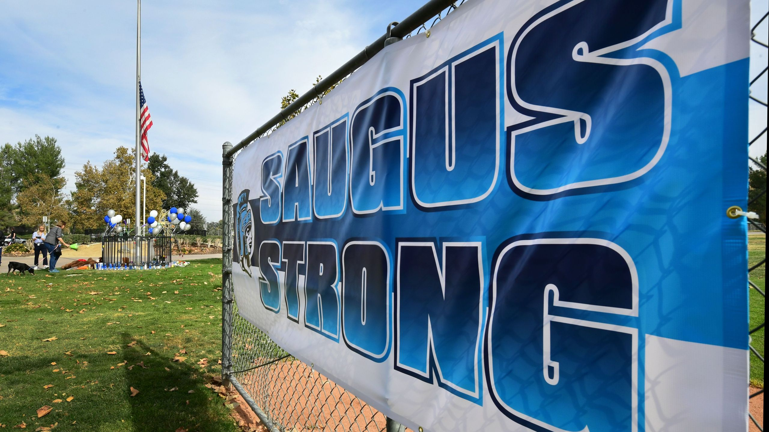 "A sign reads ""Saugus Strong"" at a makeshift memorial in Central Park, near Saugus High School, Nov. 15, 2019 in Santa Clarita. (Credit: FREDERIC J. BROWN/AFP via Getty Images)"