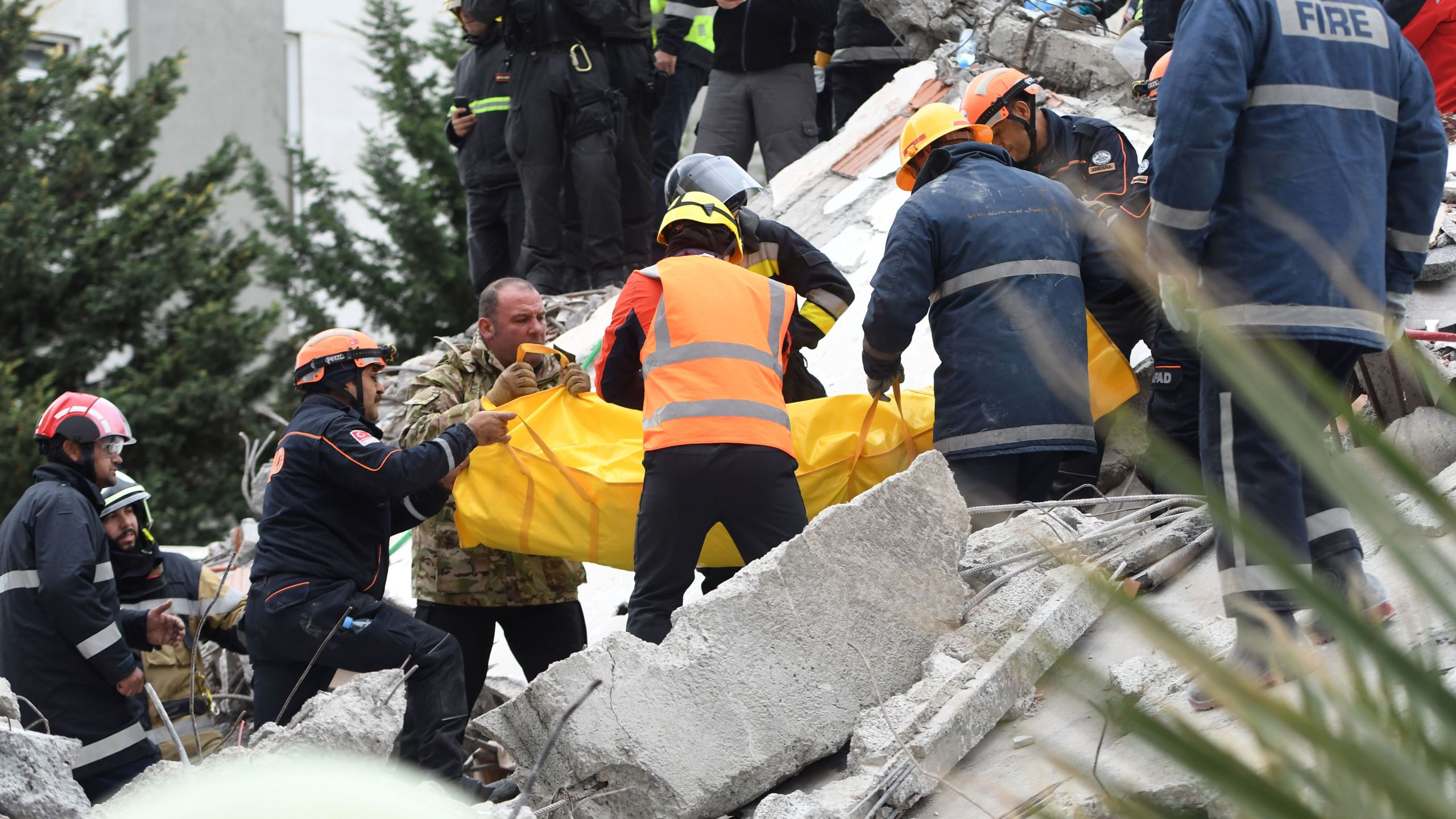 Rescue teams and firefighters carry the body of a victim found under the rubble of a collapsed building in the town of Durres, western Albania on November 28, 2019, after the strongest earthquake in decades hit the country. (Credit: GENT SHKULLAKU/AFP via Getty Images)