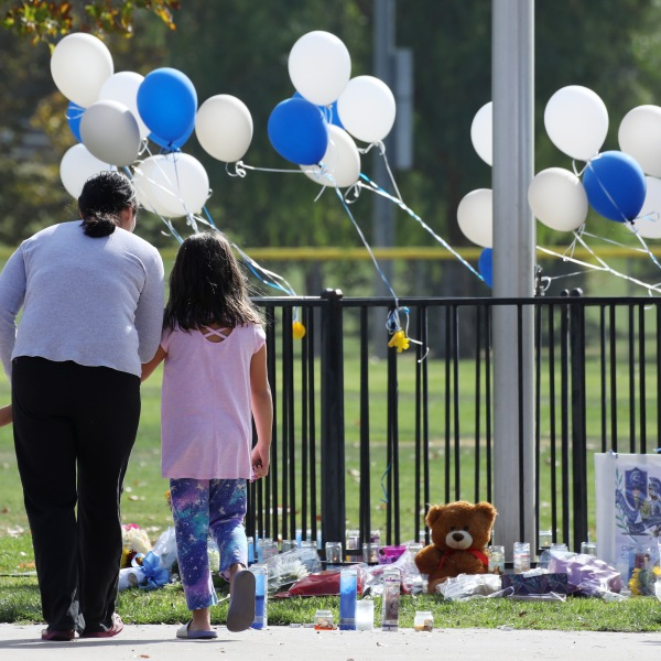 A woman and two girls visit a makeshift memorial in Central Park for victims of the shooting at nearby Saugus High School on Nov. 15, 2019 in Santa Clarita. (Credit: Mario Tama/Getty Images)