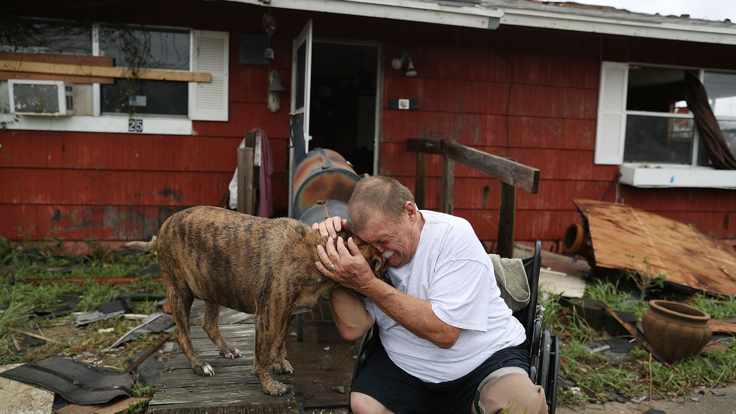 A man cries with his dog Otis after Hurricane Harvey destroyed most of his home on Aug. 26, 2017, in Rockport, Texas. (Credit: Joe Raedle/Getty Images)