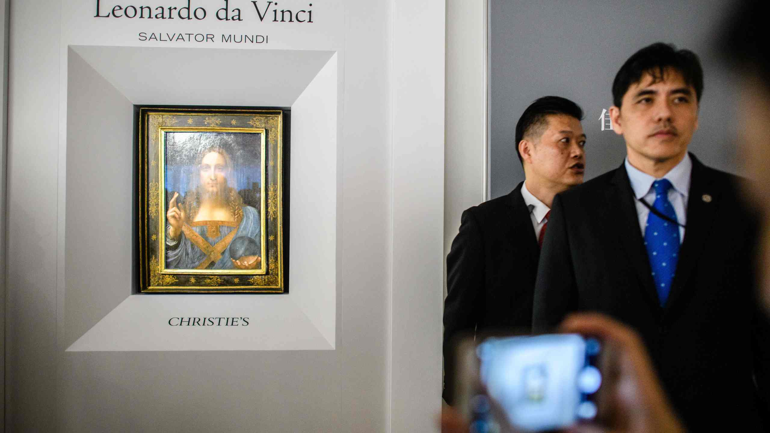 This picture taken on October 13, 2017, shows a man identified by local Hong Kong media as former CIA agent Jerry Chun Shing Lee standing in front of a member of security at the unveiling of Leonardo da Vinci's 'Salvator Mundi' painting at the Christie's showroom in Hong Kong. (Credit: Anthony Wallace/AFP via Getty Images)