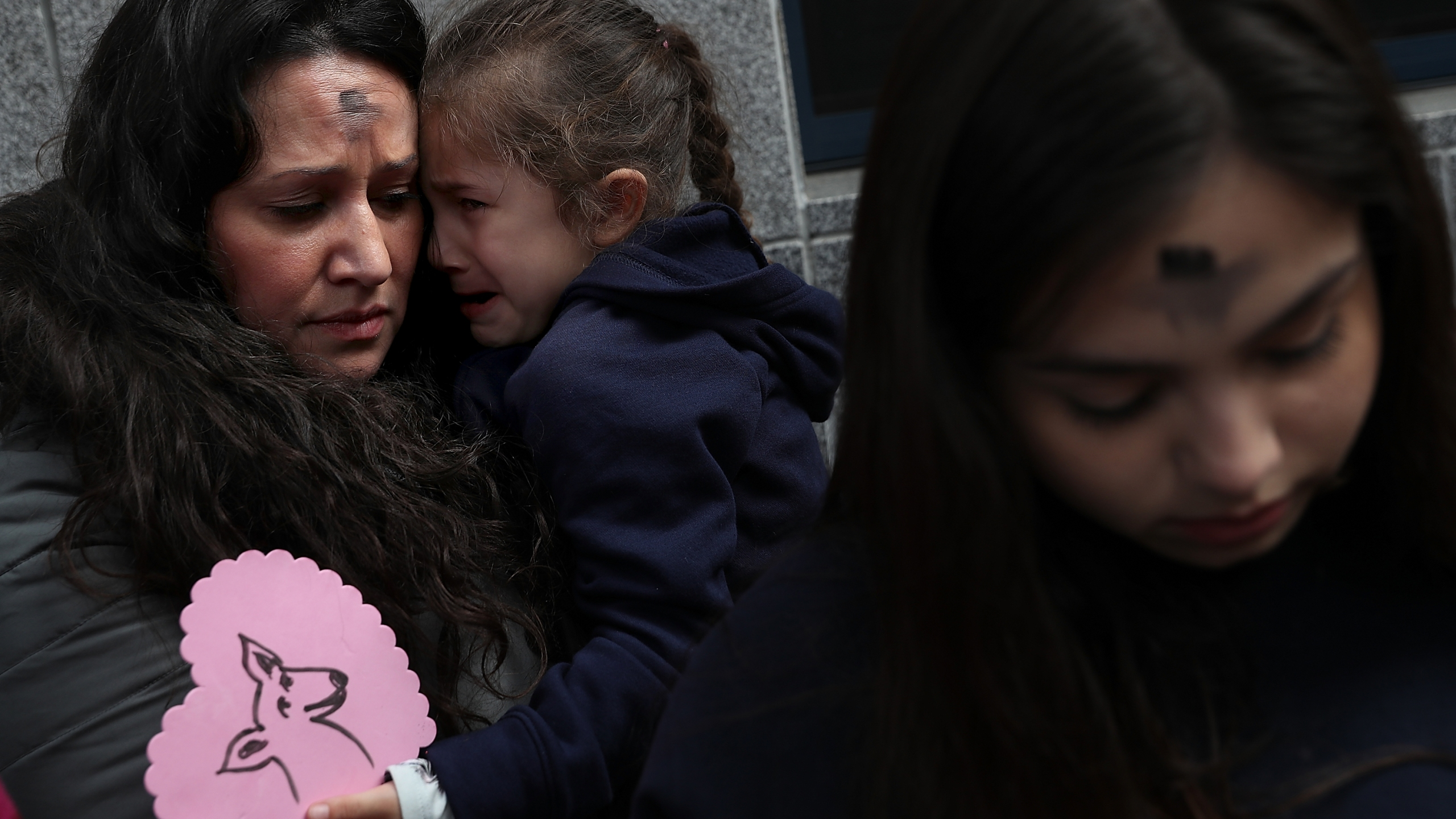 Lourdes Barraza, wife of detained immigrant Fernando Barraza, holds her crying daughter Ana Barraza during a Valentine's Day demonstration outside of the San Francisco office of the Immigration and Cutsoms Enforcement on Feb. 14, 2018 in San Francisco. (Credit: Justin Sullivan/Getty Images)