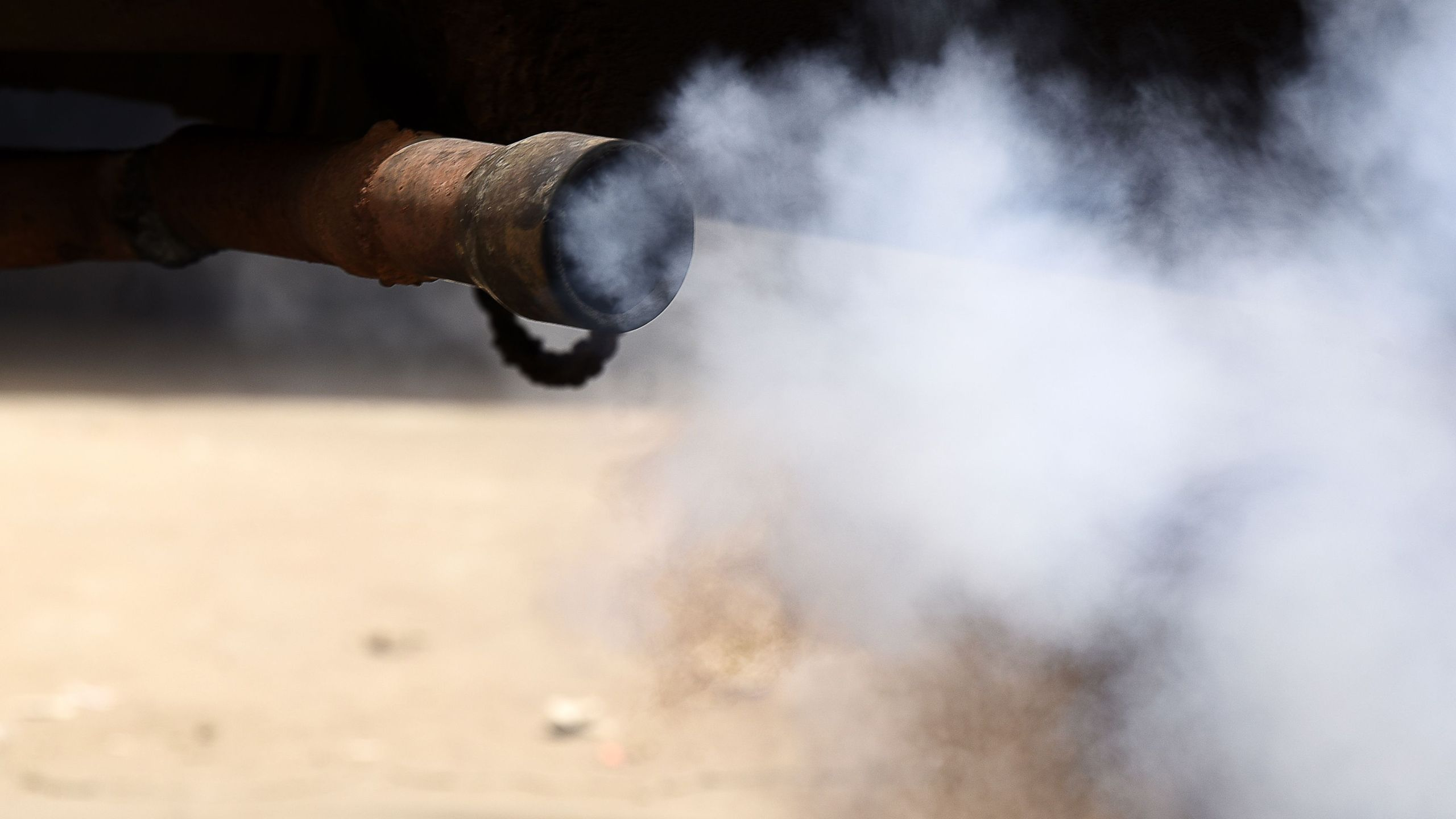 Smoke comes out of a car's exhaust pipe on June 2, 2018, in Dakar. (Credit: Seyllou/AFP via Getty Images)