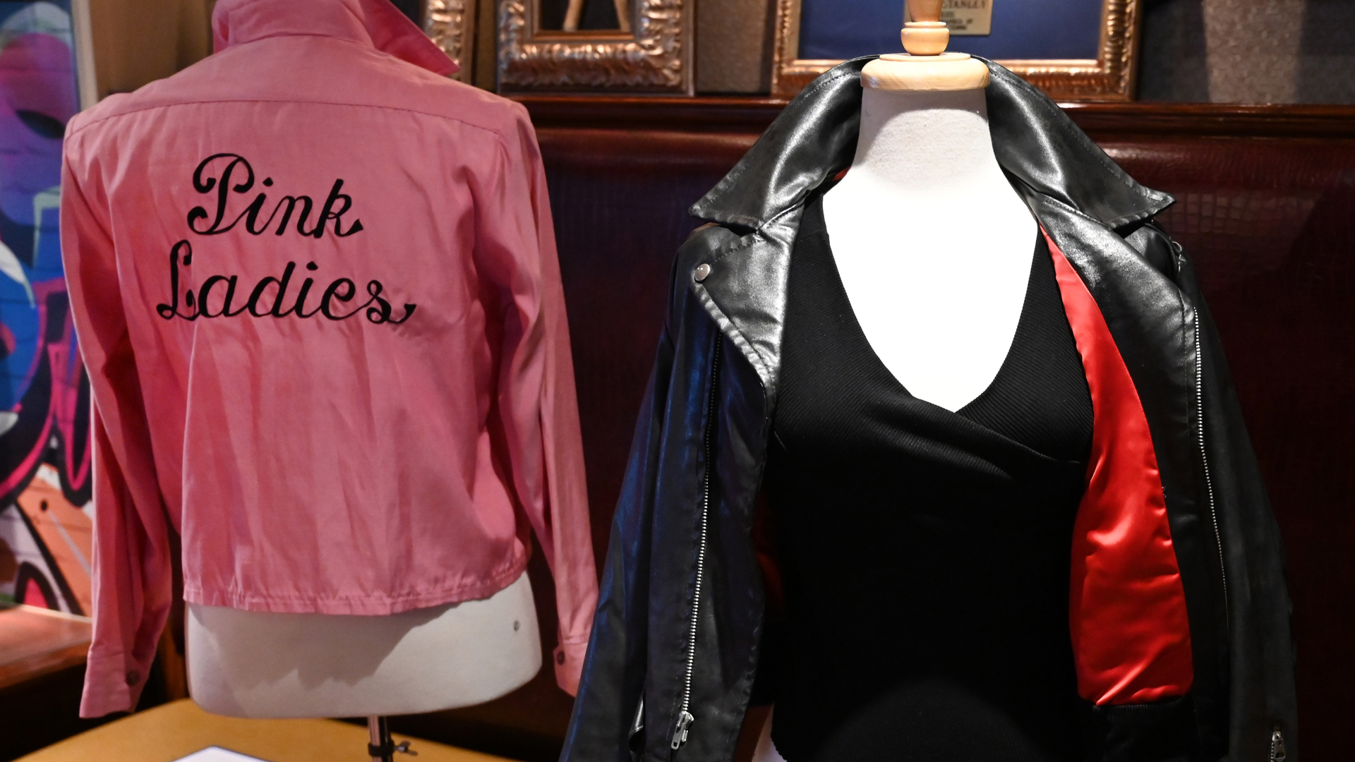 "Olivia Newton-John's famous black leather jacket worn in the blockbuster film ""Grease"" and her Grease ""Pink Ladies"" jacket worn in the film are shown during a Julien's Auctions press preview at Hard Rock Cafe in New York on October 16, 2019.(Credit: Timothy A. Clary/AFP via Getty Images)"