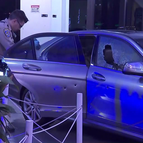 Officers investigate a car after it was involved in a shooting on the 405 Freeway in Inglewood on Nov. 11, 2019. (Credit: KTLA)