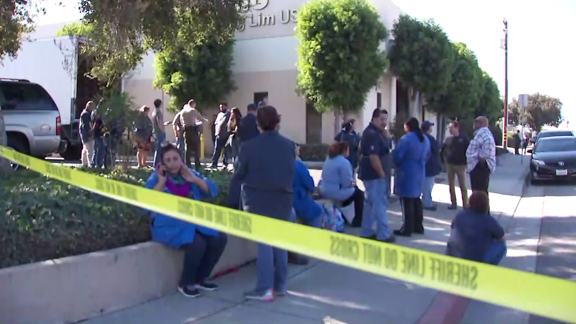 Workers wait outside after a fatal shooting at a business in Paramount on Nov. 8, 2019. (Credit: KTLA)