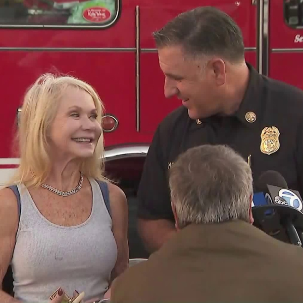 Patty Shales and Jaime Moore, assistant chief at the Los Angeles Fire Department, smile during a press briefing at a fire station in Sawtelle on Nov. 5, 2019, discussing how Shales was reunited with an heirloom that survived when the Getty Fire destroyed her Brentwood home. (Credit: KTLA)