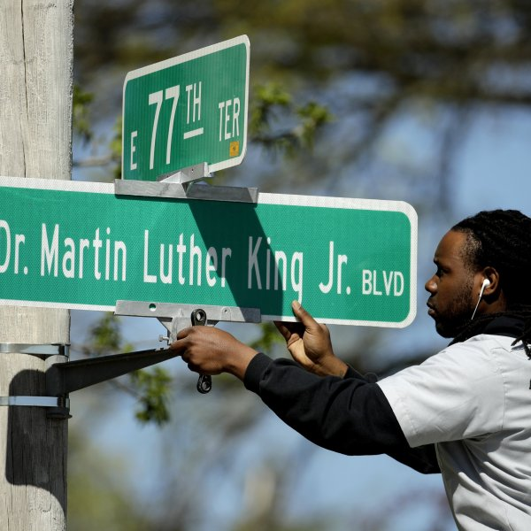A worker installs a Dr. Martin Luther King Jr. Blvd. sign in Kansas City in April 2019. (Credit: Charlie Riedel/AP via CNN Wire)