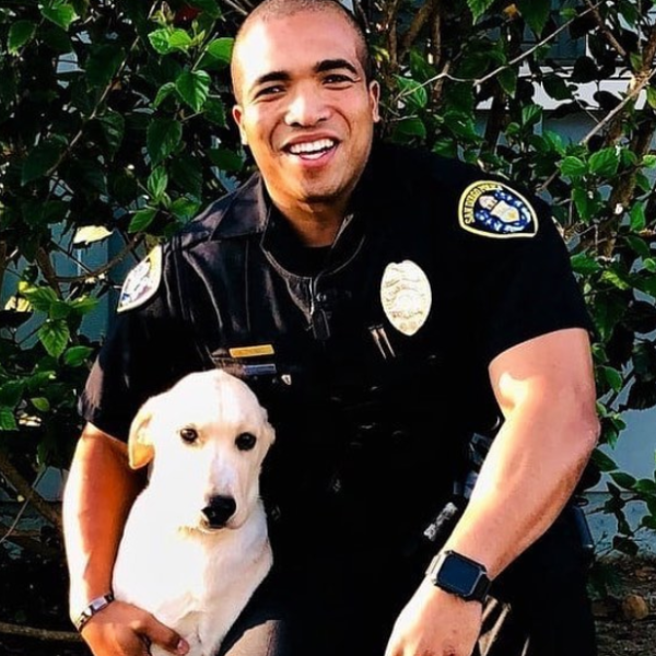 San Diego police Officer Andre Thomas poses with Victor in a photo released by city officials on Nov. 16, 2019.