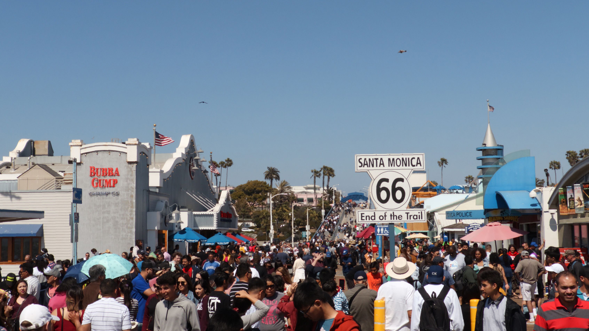 A sign marking the terminus of the historic Route 66 stands in the middle of tourists at Santa Monica Pier on April 21, 2019. (Credit: Daniel Slim / AFP / Getty Images)