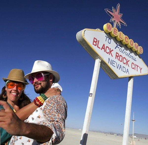 Simone Oliver of San Diego and Eric Weisz of San Francisco take a picture in front of a welcome to Black Rock City sign during the Burning Man festival in 2008. (Spencer Weiner / Los Angeles Times)