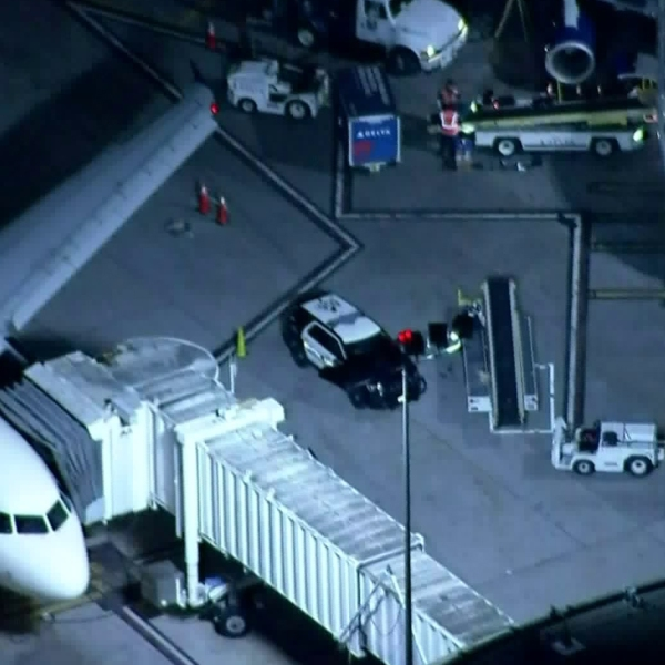 A police vehicle is seen near a Delta Air Lines planes at LAX on Dec. 26, 2019. (Credit: KTLA)