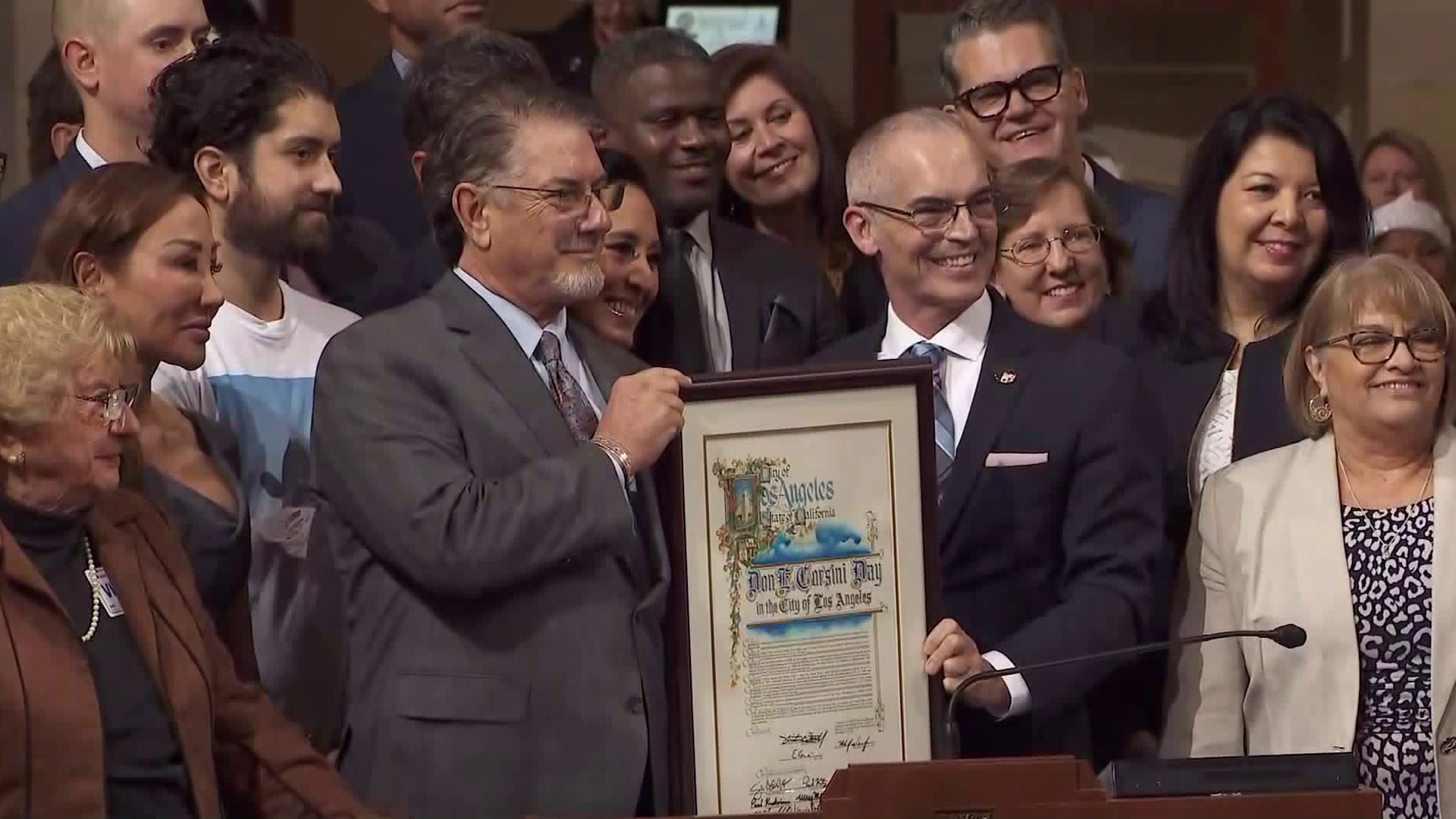 """Don Corsini, left, and Councilman Mitch O'Farrell hold a proclamation declaring Dec. 11, 2019, """"Don E. Corsini Day"""" in the city of Los Angeles. (Credit: KTLA)"""