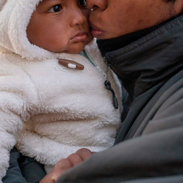 An unidentified man from Guerrero State, who is fleeing cartel violence, kisses his daughter as they prepare for another cold night in the camp on Dec. 10, 2019, in Ciudad Juarez, Mexico. In the mud and biting cold of a makeshift camp in the border city of Ciudad Juarez, more than 1,000 Mexican migrants had been waiting for weeks, some for months, for a chance to file for asylum in the United States. (Credit: PAUL RATJE/AFP via Getty Images)