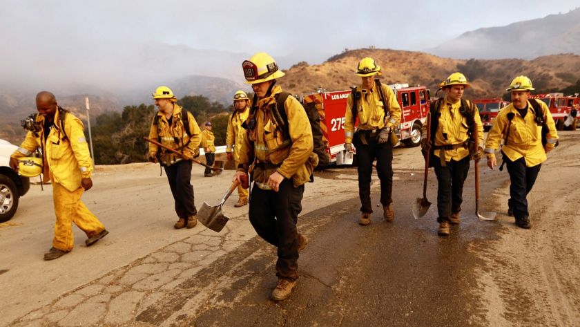 L.A. County firefighters return to their vehicles after containing a brush fire in a remote area in Sylmar in 2018.(Credit: Al Seib / Los Angeles Times)
